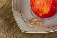 Γαμήλια δαχτυλίδια και η κόκκινη ώριμη Apple Στοκ φωτογραφία με δικαίωμα ελεύθερης χρήσης