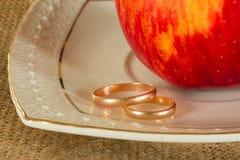 Γαμήλια δαχτυλίδια και η κόκκινη ώριμη Apple Στοκ Εικόνες