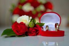 Γαμήλια δαχτυλίδια, κόκκινα τριαντάφυλλα Στοκ Εικόνες
