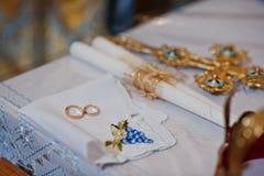 Γαμήλια δαχτυλίδια με τα κεριά και σταυρός στη γαμήλια τελετή εκκλησιών Στοκ φωτογραφία με δικαίωμα ελεύθερης χρήσης