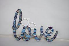 Γαμήλια δαχτυλίδια με την αγάπη λέξης Δαχτυλίδια γαμήλιου frey wille που κάθονται πάνω από το ξύλινο ρητό γραμματοσήμων; αγάπη; Στοκ εικόνες με δικαίωμα ελεύθερης χρήσης