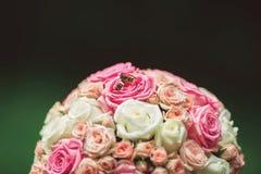 Γαμήλια δαχτυλίδια με την ανθοδέσμη, πράσινο υπόβαθρο Στοκ Φωτογραφίες