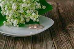 Γαμήλια δαχτυλίδια με το υπόβαθρο λουλουδιών Στοκ Φωτογραφίες