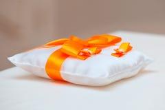 Γαμήλια δαχτυλίδια σε ένα άσπρο μαξιλάρι με την πορτοκαλιά κορδέλλα Στοκ Φωτογραφίες