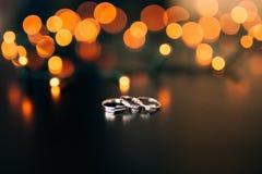 Γαμήλια δαχτυλίδια σε ένα κίτρινο υπόβαθρο bokeh των γιρλαντών μαγικός στοκ φωτογραφία