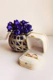 Γαμήλια δαχτυλίδια σε ένα κιβώτιο στο υπόβαθρο λουλουδιών Στοκ Φωτογραφίες