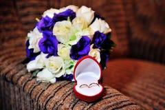 Γαμήλια δαχτυλίδια σε ένα κιβώτιο στο υπόβαθρο της ανθοδέσμης Στοκ Εικόνα
