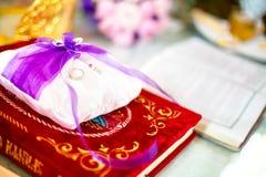 Γαμήλια δαχτυλίδια σε ένα μαξιλάρι με την ιερή Βίβλο κάτω από Στοκ Εικόνα