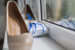 Γαμήλια δαχτυλίδια σε ένα μαλακό μαξιλάρι με την μπλε κινηματογράφηση σε πρώτο πλάνο κορδελλών Στοκ φωτογραφίες με δικαίωμα ελεύθερης χρήσης