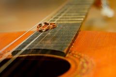 Γαμήλια δαχτυλίδια σε μια κιθάρα Στοκ φωτογραφία με δικαίωμα ελεύθερης χρήσης