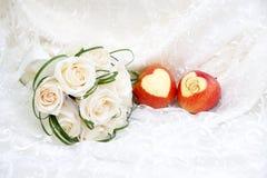 Γαμήλια δαχτυλίδια στα μήλα και την ανθοδέσμη Στοκ Φωτογραφία