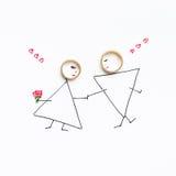 Γαμήλια δαχτυλίδια στην εικόνα με τη νύφη και το νεόνυμφο Στοκ εικόνα με δικαίωμα ελεύθερης χρήσης