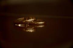 Γαμήλια δαχτυλίδια στον πίνακα με την αντανάκλαση Στοκ Εικόνες