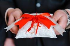 Γαμήλια δαχτυλίδια στο διακοσμητικό άσπρο μαξιλάρι Στοκ εικόνες με δικαίωμα ελεύθερης χρήσης