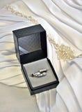 Γαμήλια δαχτυλίδια στο κιβώτιο με το υπόβαθρο γαμήλιων φορεμάτων Στοκ Φωτογραφίες
