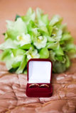 Γαμήλια δαχτυλίδια στο κόκκινο κιβώτιο στην πράσινη ανθοδέσμη Στοκ Εικόνες