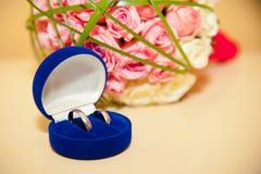 Γαμήλια δαχτυλίδια στο μπλε κιβώτιο στο υπόβαθρο του β της νύφης Στοκ φωτογραφία με δικαίωμα ελεύθερης χρήσης