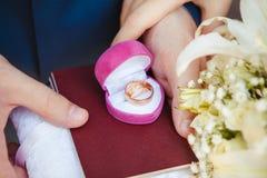 Γαμήλια δαχτυλίδια στο ρόδινο κιβώτιο στο πιστοποιητικό γάμου Στοκ Φωτογραφία