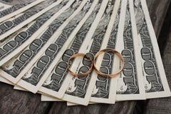 Γαμήλια δαχτυλίδια στο υπόβαθρο των χρημάτων Στοκ εικόνα με δικαίωμα ελεύθερης χρήσης