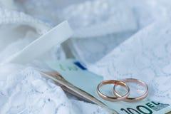Γαμήλια δαχτυλίδι και τραπεζογραμμάτια στο νυφικό υπόβαθρο φορεμάτων δαντελλών Marr στοκ φωτογραφία