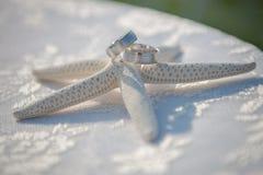 Γαμήλια γυαλιά και δαχτυλίδια στα κοχύλια και τον αστερία Πίνακας με την κάλυψη δαντελλών Στοκ Εικόνες