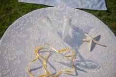 Γαμήλια γυαλιά και δαχτυλίδια στα κοχύλια και τον αστερία Πίνακας με την κάλυψη δαντελλών Στοκ Φωτογραφία