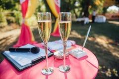 Γαμήλια γυαλιά που γεμίζουν με τη σαμπάνια στο συμπόσιο Στοκ Εικόνα