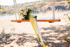 Γαμήλια διακόσμηση μιας όμορφης λεπτής ανθοδέσμης που ξαπλώνει σε μια ταλάντευση στο πάρκο Στοκ φωτογραφία με δικαίωμα ελεύθερης χρήσης
