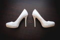 Γαμήλια νυφικά παπούτσια και δαχτυλίδια στο σκοτεινό ξύλινο υπόβαθρο Στοκ φωτογραφία με δικαίωμα ελεύθερης χρήσης