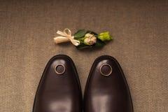 Γαμήλια παπούτσια, μπουτονιέρα, και δαχτυλίδι Στοκ Εικόνες