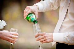 Γαμήλια ποτήρια της σαμπάνιας στα χέρια του νεόνυμφου Στοκ εικόνες με δικαίωμα ελεύθερης χρήσης