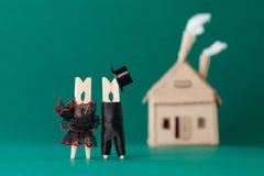 Γαμήλια πρόσκληση και έννοια αγάπης Χαρακτήρες γόμφων νεόνυμφων νυφών clothespin, σπίτι χαρτονιού στο πράσινο υπόβαθρο Περίληψη στοκ εικόνες με δικαίωμα ελεύθερης χρήσης