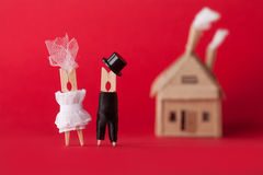 Γαμήλια πρόσκληση και έννοια αγάπης Χαρακτήρες γόμφων νεόνυμφων νυφών clothespin, σπίτι χαρτονιού στο κόκκινο υπόβαθρο Περίληψη στοκ φωτογραφία με δικαίωμα ελεύθερης χρήσης