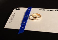 Γαμήλια πρόσκληση με τα δαχτυλίδια που απομονώνονται στο μαύρο υπόβαθρο Στοκ Εικόνες