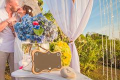 Γαμήλια πλαίσιο και honeymooners στο υπόβαθρο Στοκ Φωτογραφίες