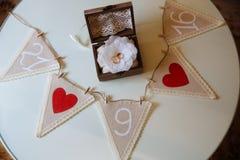 Γαμήλια χρυσά δαχτυλίδια σε ένα ξύλινο κιβώτιο στο άσπρο υπόβαθρο η ημερομηνία σώζει Στοκ Εικόνες