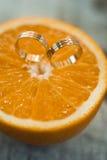 Γαμήλια χρυσά δαχτυλίδια στα πορτοκαλιά φρούτα Στοκ Εικόνες
