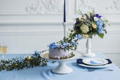Γαμήλιες διακοσμήσεις με τα κεριά, το κέικ και τα όμορφα λουλούδια Στοκ εικόνα με δικαίωμα ελεύθερης χρήσης