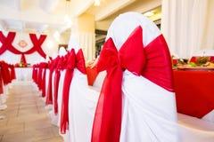 Γαμήλιες καρέκλες για τους φιλοξενουμένους με τις κόκκινες κορδέλλες Στοκ εικόνες με δικαίωμα ελεύθερης χρήσης