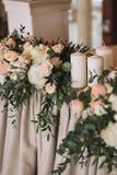 Γαμήλιος πίνακας που διακοσμείται με τις ανθοδέσμες λουλουδιών με τα τριαντάφυλλα, peonies, τον ευκάλυπτο και τα κεριά Στοκ Φωτογραφία