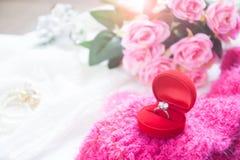 Γαμήλιο δαχτυλίδι, δαχτυλίδι διαμαντιών στο κόκκινο κιβώτιο με τα ρόδινα τριαντάφυλλα Στοκ εικόνες με δικαίωμα ελεύθερης χρήσης