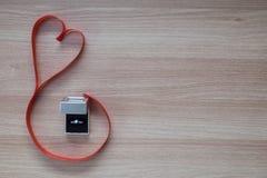Γαμήλιο δαχτυλίδι και κόκκινη κορδέλλα καρδιών στην ξύλινη επιφάνεια με το κενό s Στοκ φωτογραφία με δικαίωμα ελεύθερης χρήσης