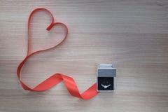 Γαμήλιο δαχτυλίδι και κόκκινη κορδέλλα καρδιών στην ξύλινη επιφάνεια με το κενό s Στοκ Φωτογραφία