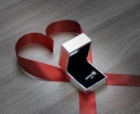 Γαμήλιο δαχτυλίδι και κόκκινη κορδέλλα καρδιών στην ξύλινη επιφάνεια Στοκ Εικόνες