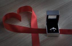 Γαμήλιο δαχτυλίδι και κόκκινη κορδέλλα καρδιών στην ξύλινη επιφάνεια Στοκ εικόνα με δικαίωμα ελεύθερης χρήσης