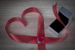 Γαμήλιο δαχτυλίδι και κόκκινη κορδέλλα καρδιών στην ξύλινη επιφάνεια Στοκ φωτογραφία με δικαίωμα ελεύθερης χρήσης