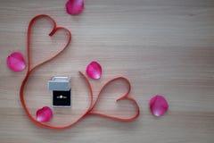 Γαμήλιο δαχτυλίδι και κόκκινη κορδέλλα καρδιών δύο με τα ρόδινα ροδαλά πέταλα στο W Στοκ Εικόνες