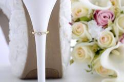 Γαμήλιο δαχτυλίδι στο όμορφο άσπρο τακούνι παπουτσιών στιλέτων στοκ εικόνες