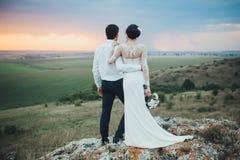 Γαμήλιο ζεύγος που κοιτάζει στο λόφο βουνών στο ηλιοβασίλεμα στοκ εικόνα
