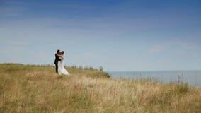 Γαμήλιο ζεύγος που στέκεται ενάντια στο μπλε ουρανό φιλμ μικρού μήκους